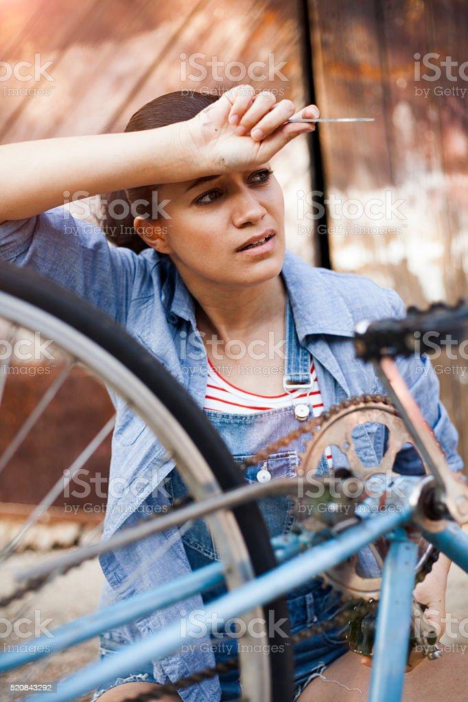 young woman repairing a bike stock photo