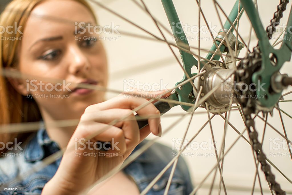 Young woman repairing her bicycle. Focus on  girl's hand. stock photo