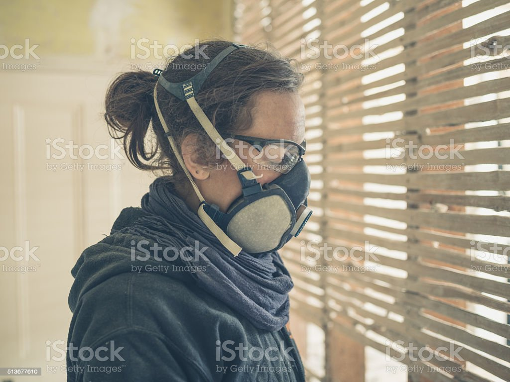 Young woman repairing wattle and daub wall stock photo