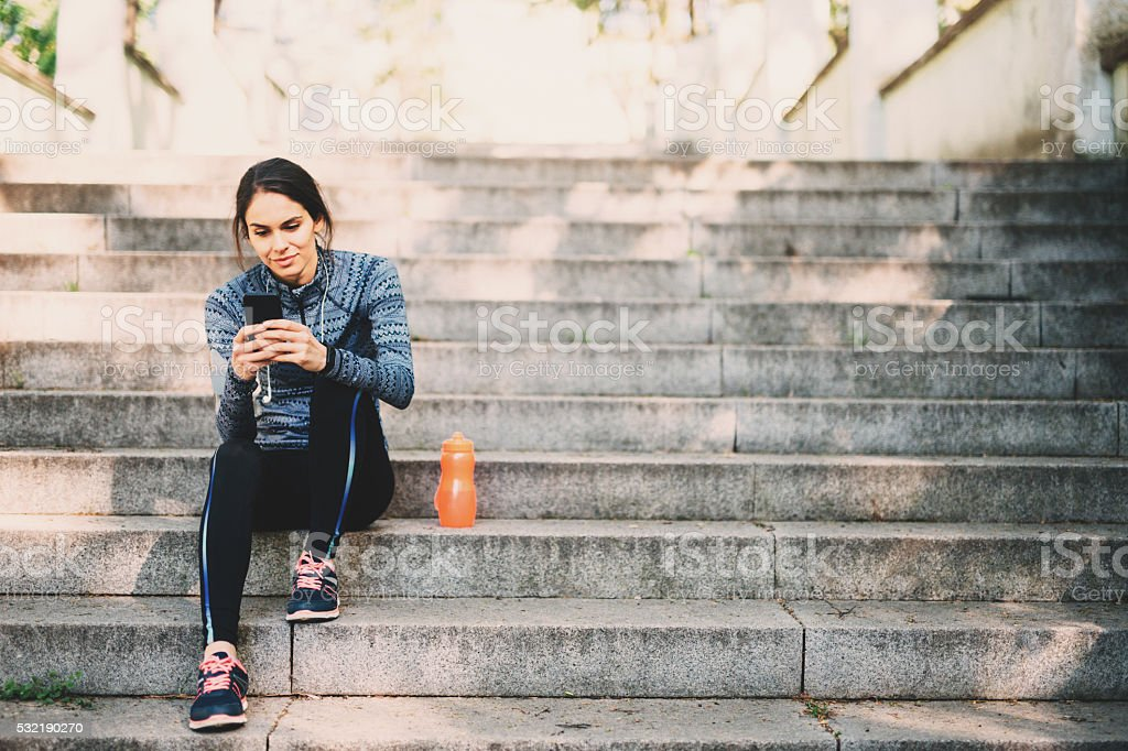 Young woman resting after jogging in the park stock photo