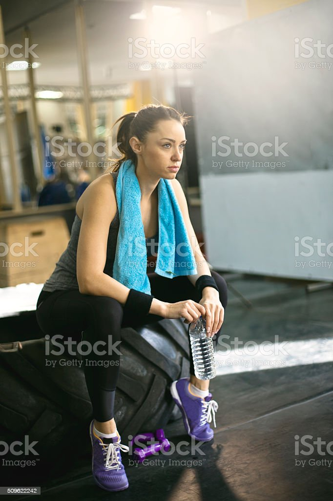 Young woman resting after workout at gym stock photo