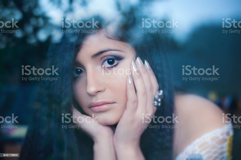 Young woman resting chin on hand and looking at camera. stock photo