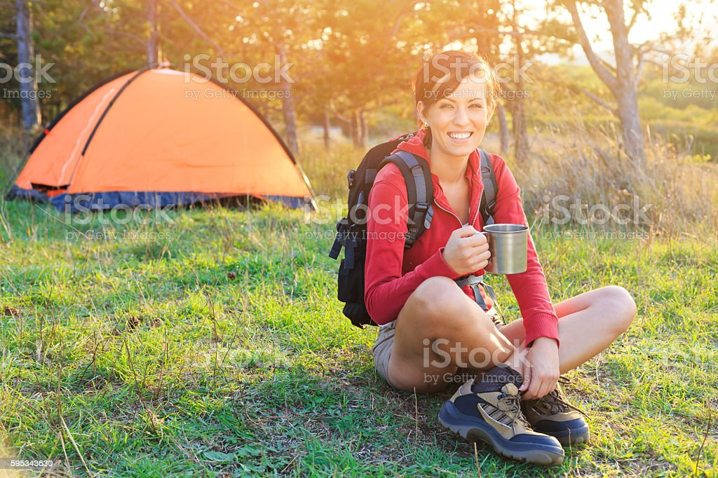 Young woman resting in front of a tent stock photo