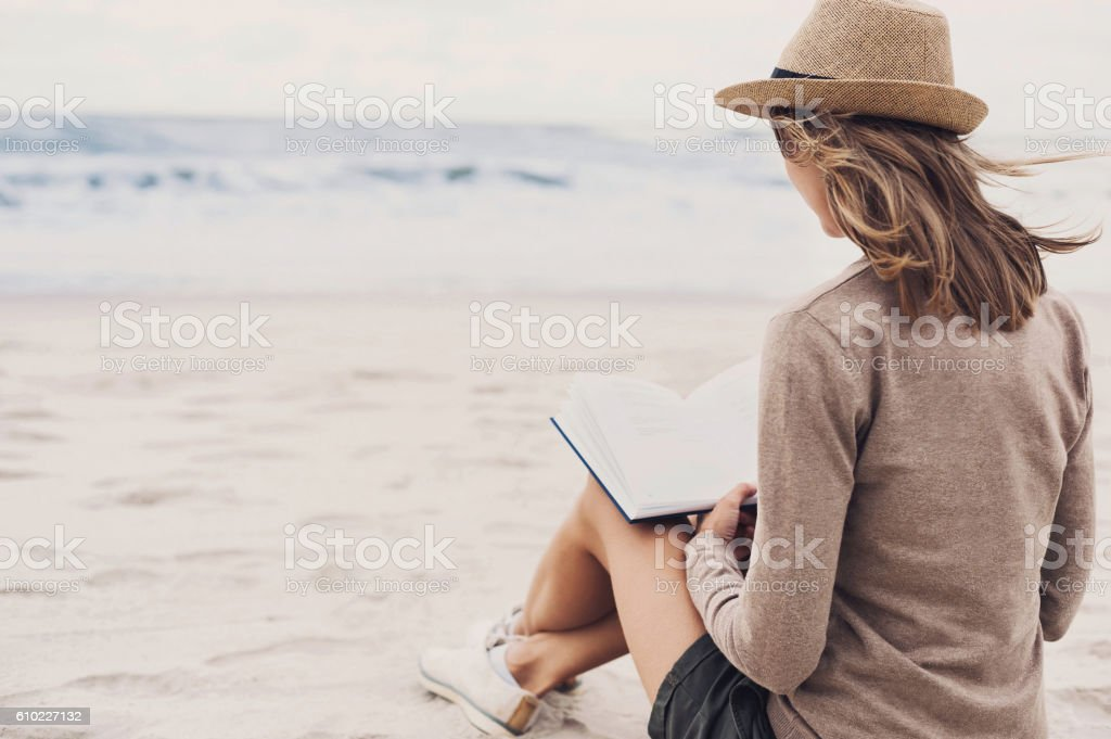Young woman resting on a beach in autumn stock photo