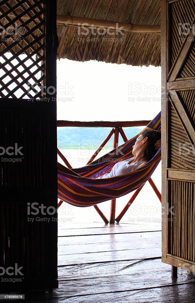 Young woman resting on a hammock in Yandup Island lodge stock photo
