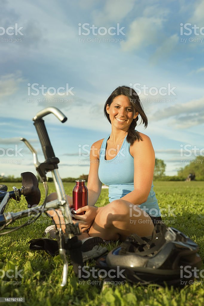 Young Woman Resting on Grass After Bicycle Exercise royalty-free stock photo