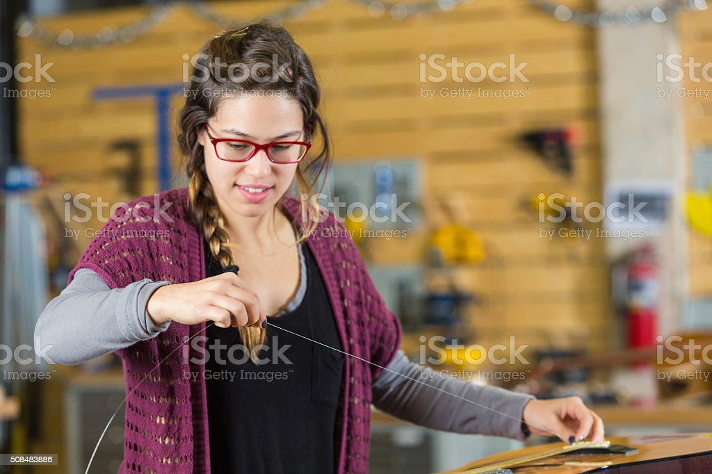 Young woman re-strings guitar in music store stock photo