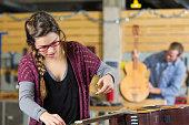 Young woman re-strings guitar in repair shop