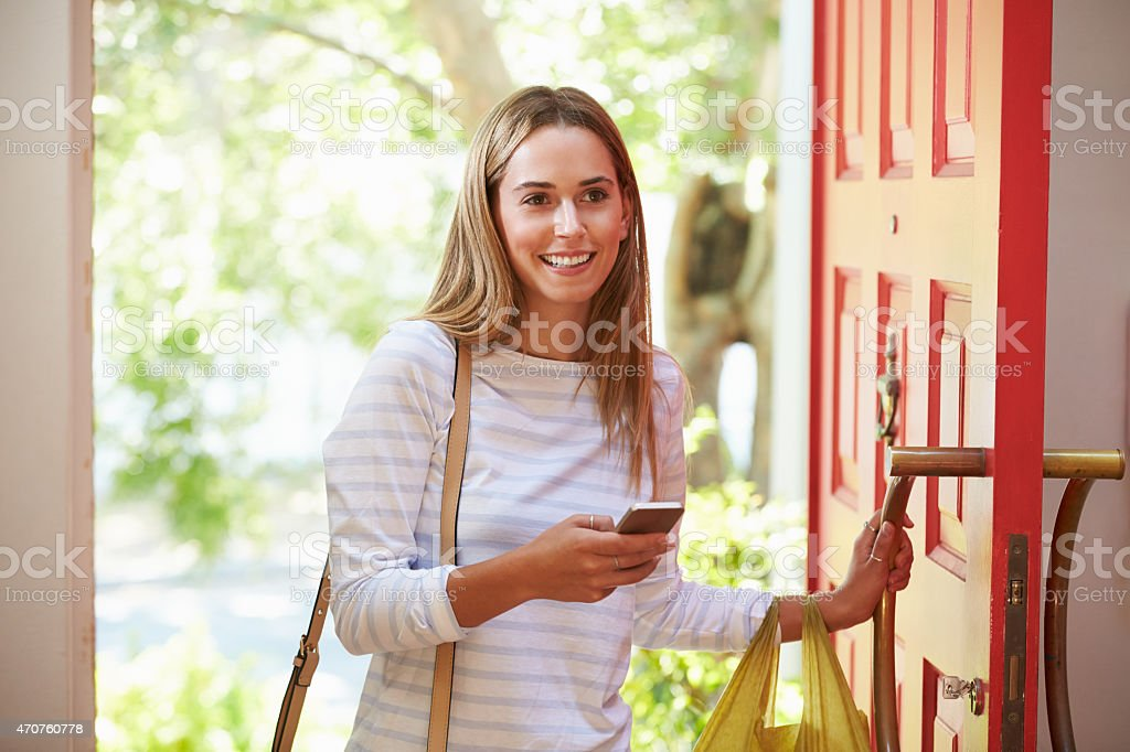 Young Woman Returning Home For Work With Shopping stock photo