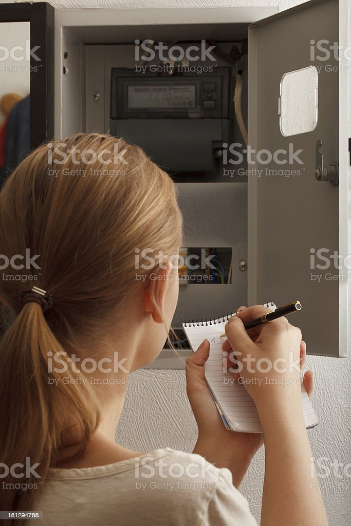 Young woman rewrites the electrical meter readings stock photo