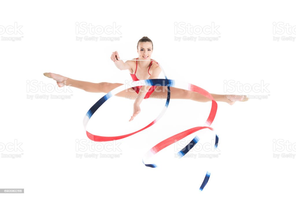 young woman rhythmic gymnast jumping with colorful rope and looking at camera stock photo