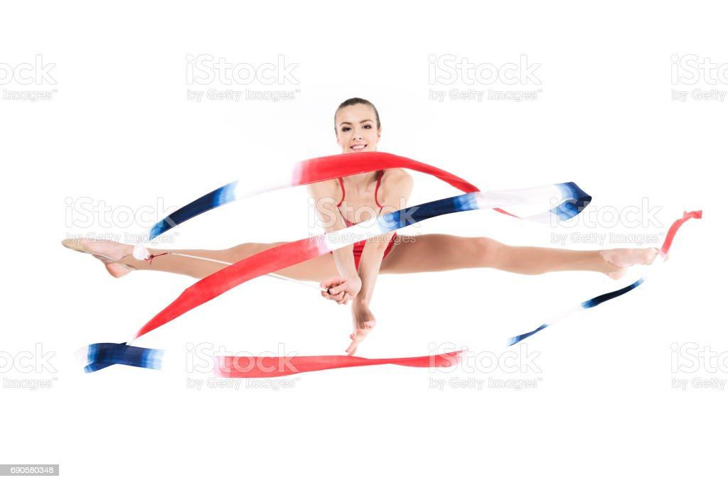 young woman rhythmic gymnast jumping with rope and looking at camera stock photo