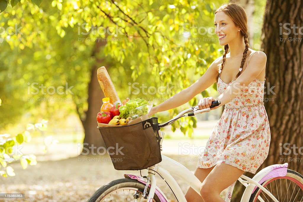 Young Woman Ride Bicycle with shopping bag full of groceries. stock photo