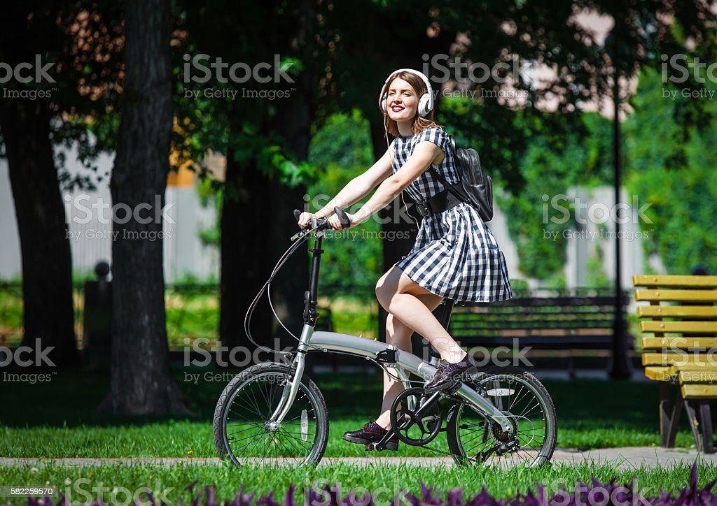 Young woman rides bicycle in the park stock photo