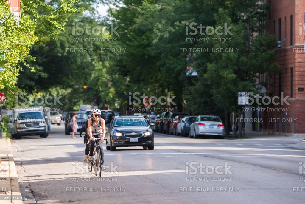 Young woman riding a bike through North Center in Chicago stock photo