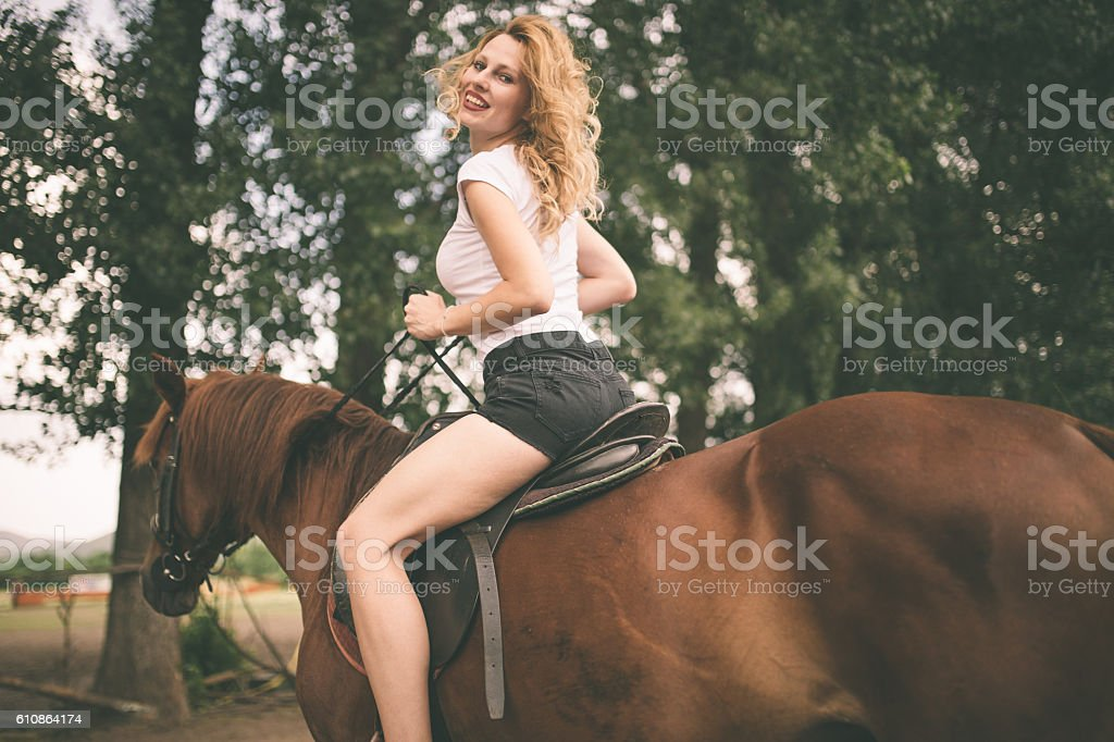 Young woman riding a horse looking back stock photo