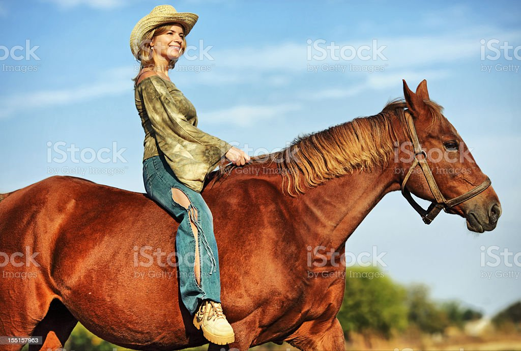 Young woman riding a horse outdoor royalty-free stock photo