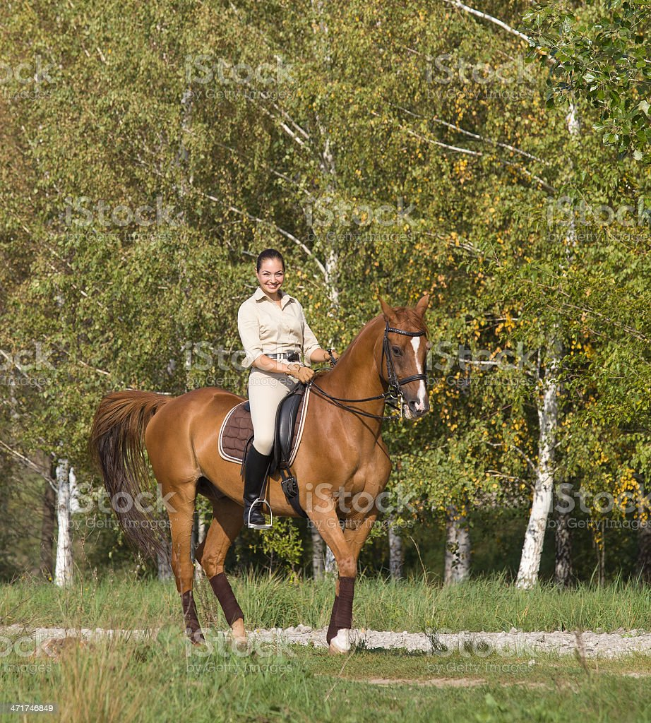 Young woman riding a horse through woodland royalty-free stock photo