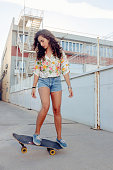 young woman riding a skateboard in abandoned industrial area