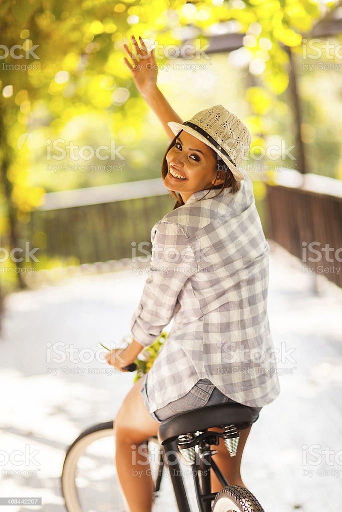 young woman riding her bike waving goodbye stock photo