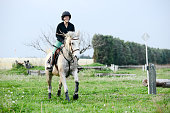 young woman riding horse training jump hurdle equitation competition outdoor