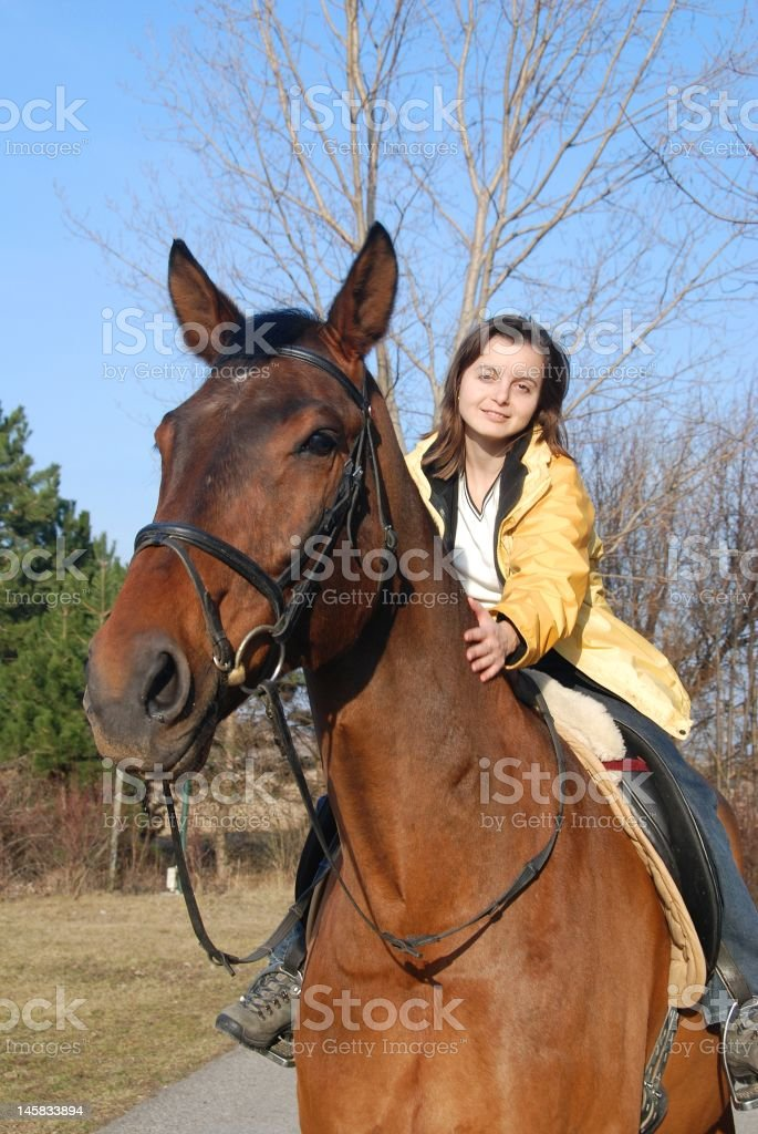 Young woman riding on big brown horse royalty-free stock photo
