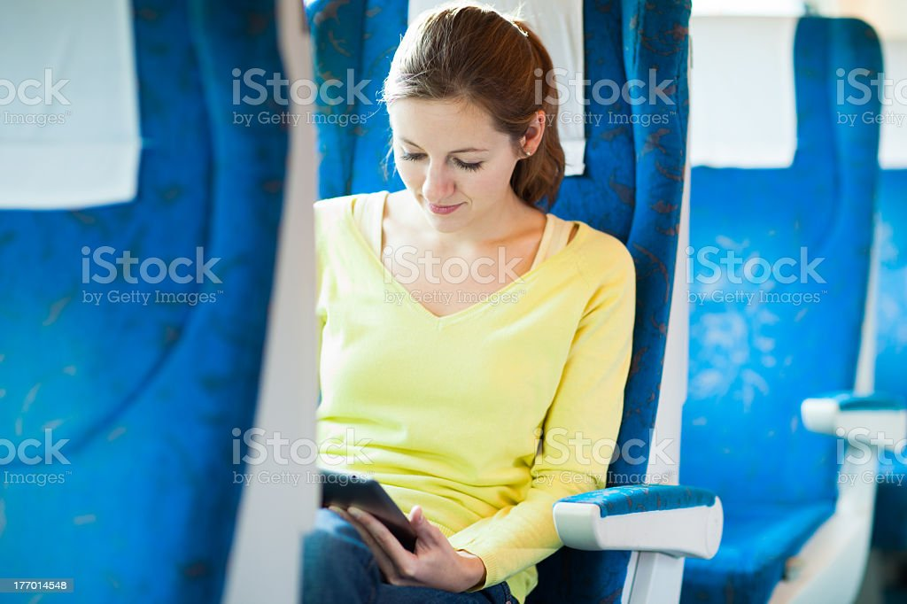 Young woman riding the train using her tablet royalty-free stock photo