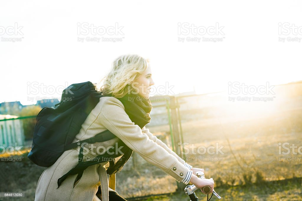 Young Woman Riding Through An Abandoned Neighbourhood In The Evening stock photo