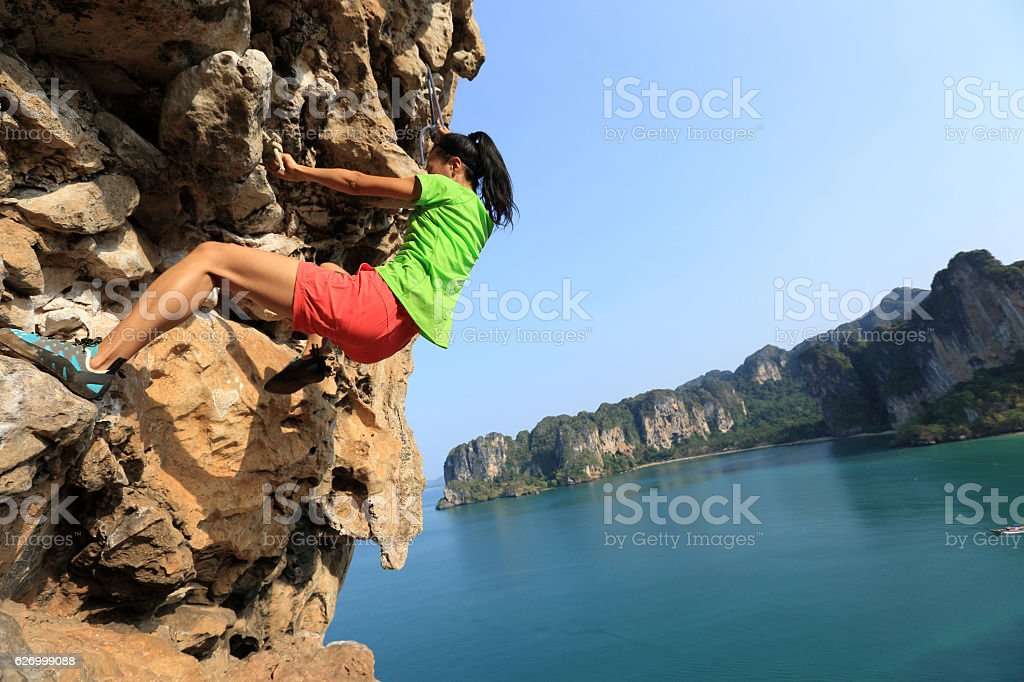 young woman rock climber climbing at seaside cliff stock photo