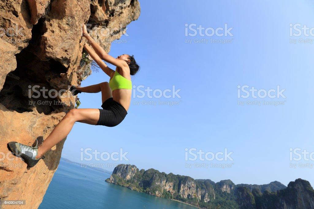 young woman rock climber climbing at seaside mountain rock stock photo