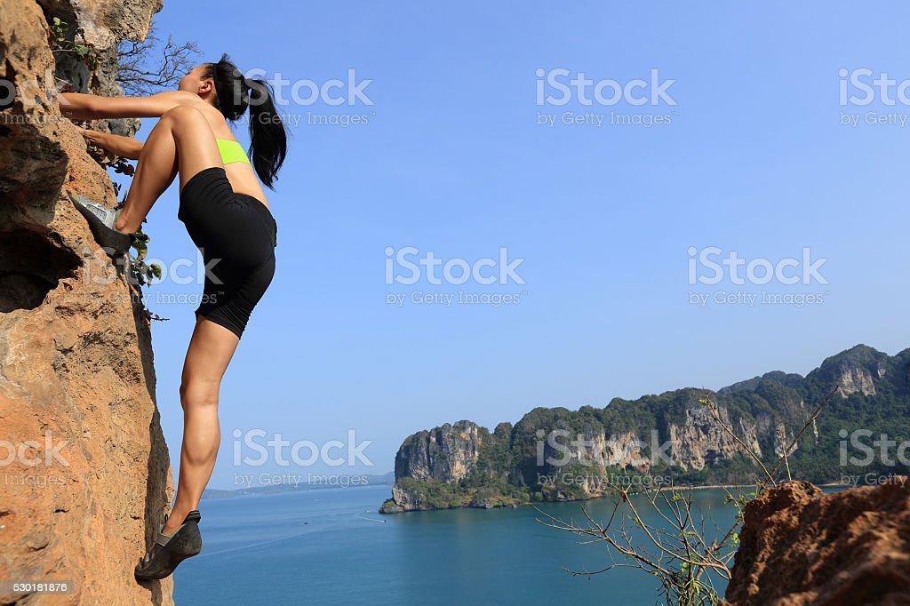 young woman rock climber climbing on seaside mountain cliff stock photo