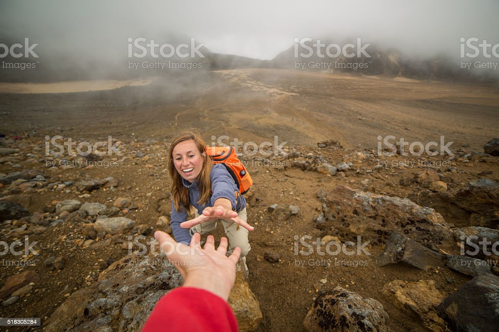 Young woman rock climbing, partner giving a helping hand stock photo