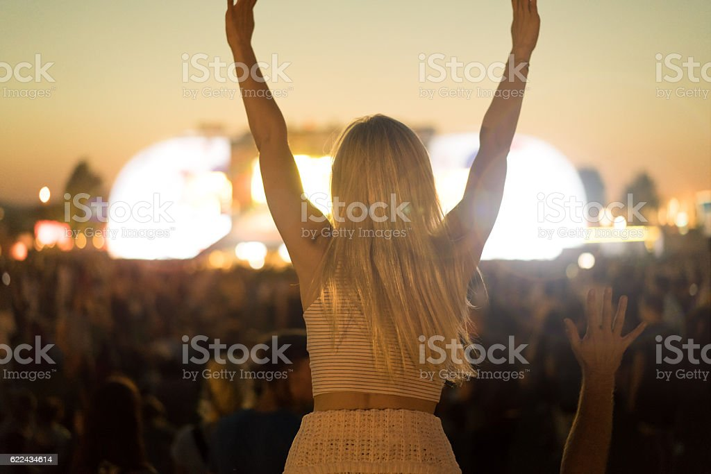 young woman rock concert sitting on shoulders of friend stock photo