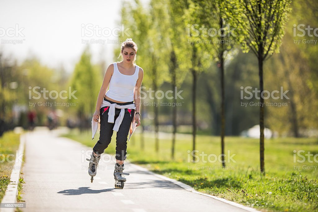 Young woman roller skating during spring day in the park. stock photo