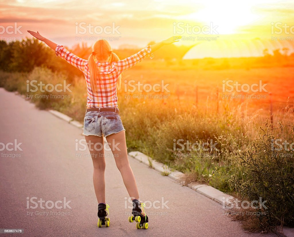 Young woman roller skating on empty road stock photo
