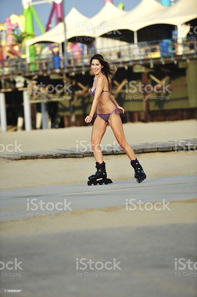 Young Woman Rollerblading on Santa Monica Beach near Pier royalty-free stock photo