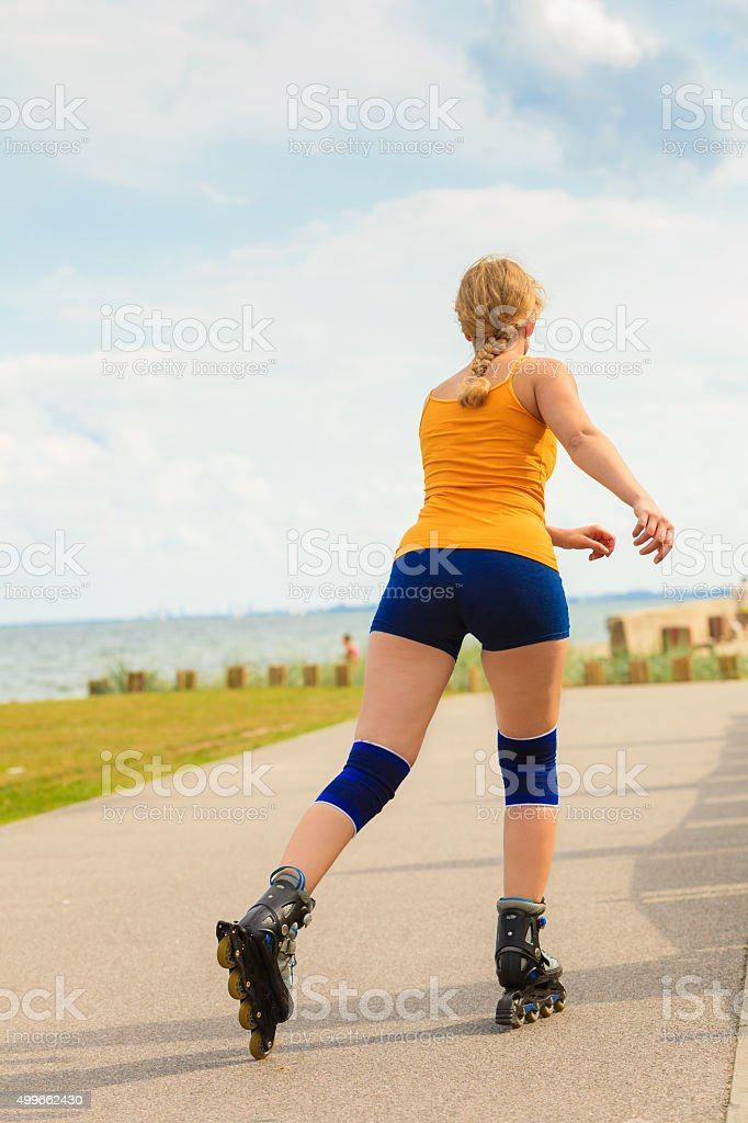 Young woman rollerblading outdoor on sunny day stock photo