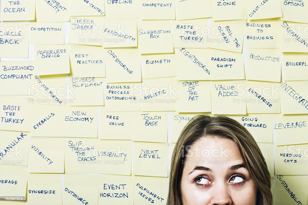 Young woman rolls eyes at excess business buzzwords on noticeboard stock photo