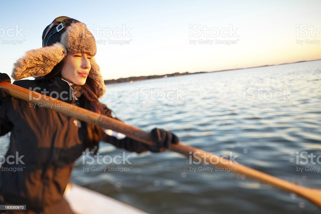 Young woman rowing a boat in winter royalty-free stock photo