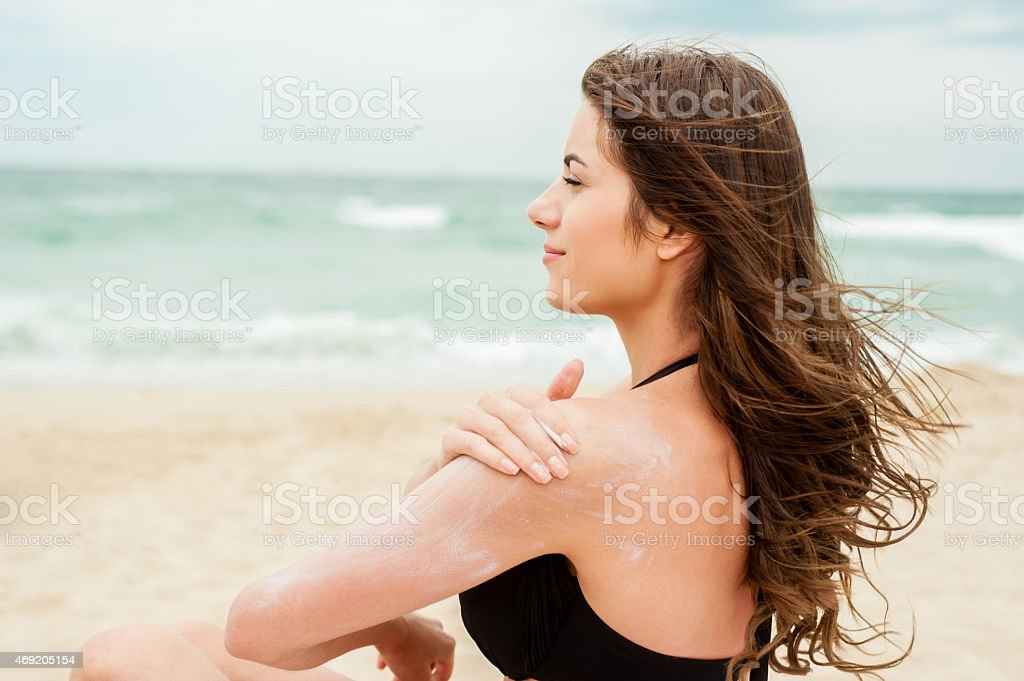 Young woman rubbing in sun lotion by the sea stock photo