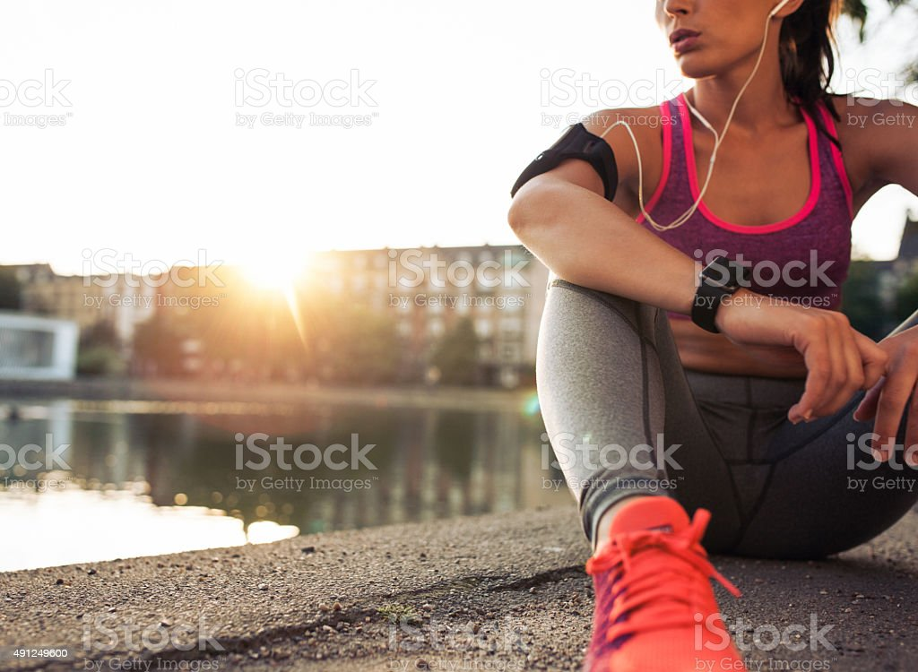 Young woman runner resting along pond stock photo