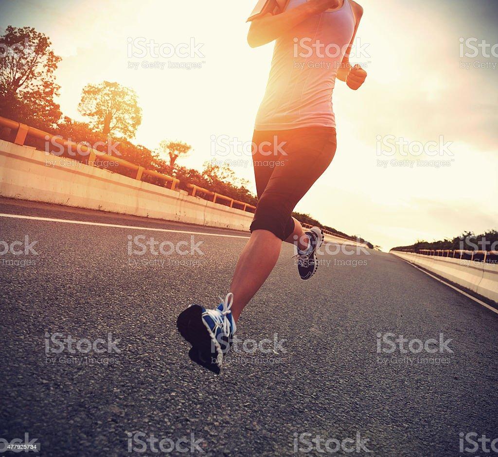 young woman runner  running on city bridge road stock photo