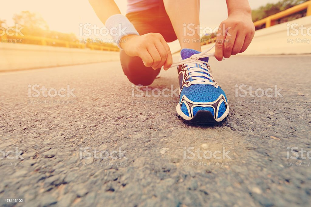 young woman runner tying shoelaces on city road stock photo