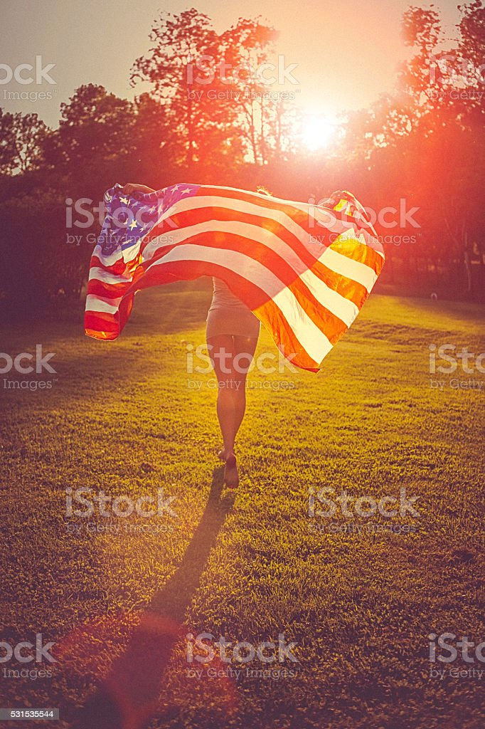 Young woman running across a meadow holding american flag stock photo