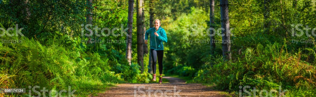 Young woman running along summer forest trail green woodland panorama stock photo