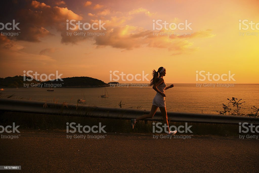 Young woman running at sunset royalty-free stock photo