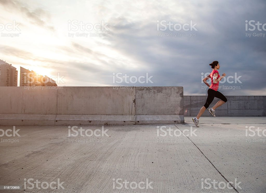 Young woman running at urban place stock photo