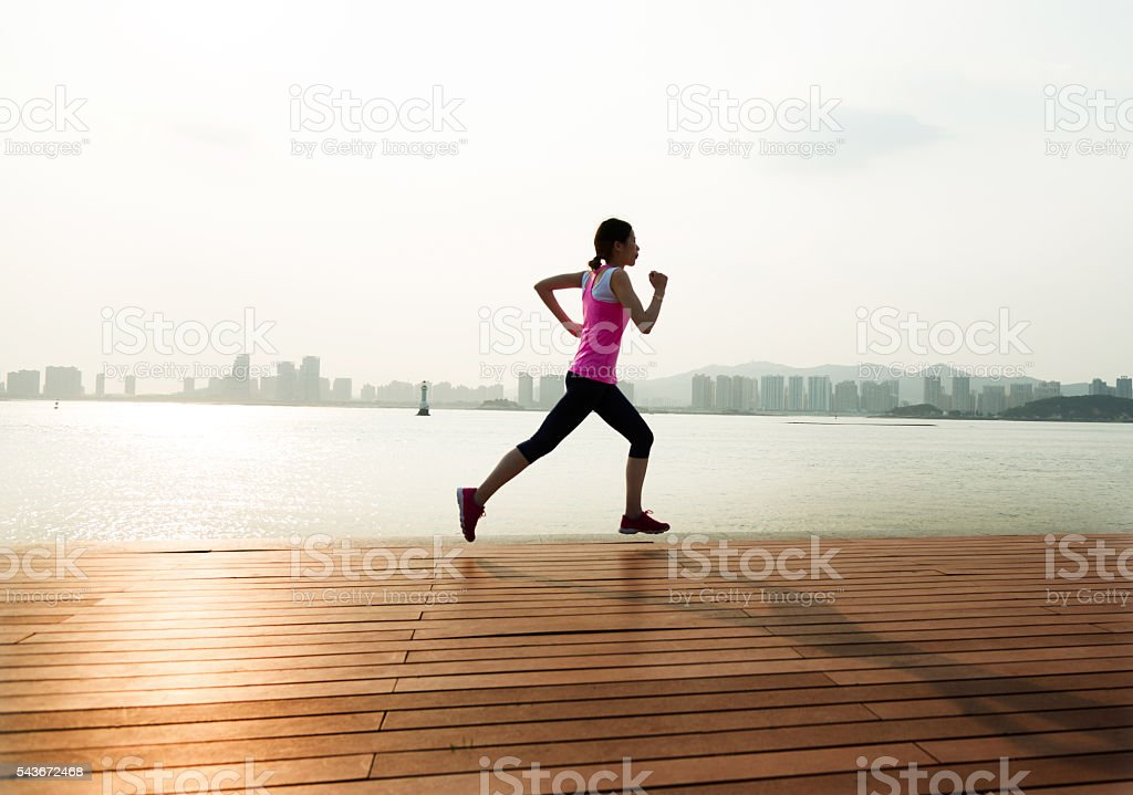 Young woman running at wooden boardwalk stock photo