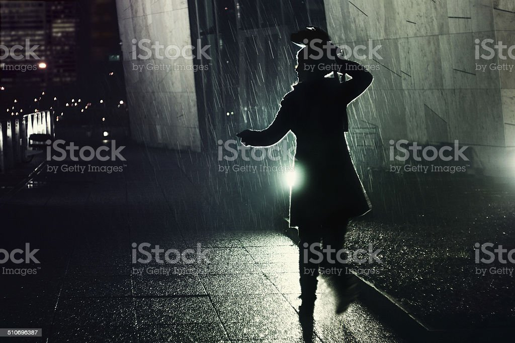 young woman running away from the rain stock photo