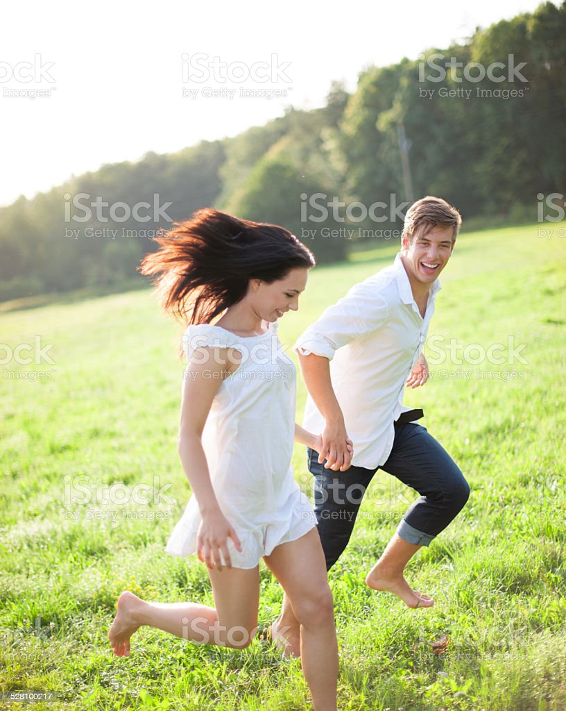 Young woman running barfoot over meadow stock photo